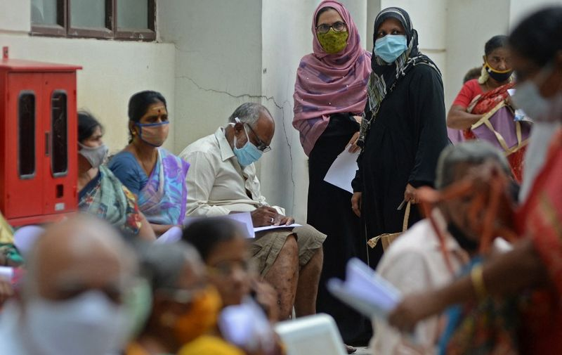 People wait for their turn to receive the Covid-19 coronavirus vaccine at a government hospital in Chennai on April 16, 2021. (Photo by Arun SANKAR / AFP)