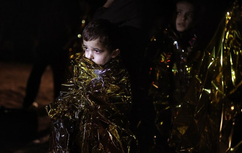 A boy looks on after arriving with other migrants and refugees on the Greek island of Lesbos on October 7, 2015, after crossing the Aegean sea from Turkey. Greek premier Alexis Tsipras said on October 6 that Athens would upgrade its refugee facilities by November to tackle the growing influx from Syria as the EU pledged 600 extra staff to help. Europe is grappling with its biggest migration challenge since World War II, with the main surge coming from civil war-torn Syria. AFP PHOTO / ARIS MESSINIS