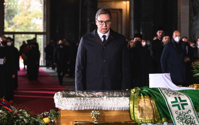 Serbian President Aleksandar Vucic pays his last respect next to the casket of late Serbian patriarch Irinej during a funeral service at Belgrade's Saint Sava temple, on November 22, 2020. - Patriarch Irinej, the head of the Serbian Orthodox Church, died of coronavirus on November 20, 2020, three weeks after his unofficial second-in-command also succumbed to Covid-19, the church said. (Photo by Andrej ISAKOVIC / AFP)