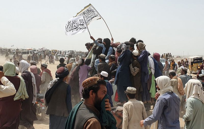 People wave Taliban flags as they drive through the Pakistani border town of Chaman on July 14, 2021, after the Taliban claimed they had captured the Afghan side of the border crossing of Spin Boldak along the frontier with Pakistan. (Photo by Asghar ACHAKZAI / AFP)