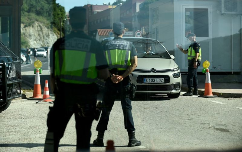 Spanish border police officers stand guard at a checkpoint as a car crosses the French-Spanish border at La Jonquera on June 21, 2020. - Traffic flowed again across Spain's border with France as the last of the strict Spanish coronavirus restrictions introduced in March were eased. (Photo by Josep LAGO / AFP)