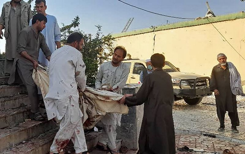 EDITORS NOTE: Graphic content / Afghan men carry the dead body of a victim to an ambulance after a bomb attack at a mosque in Kunduz on October 8, 2021. (Photo by - / AFP)