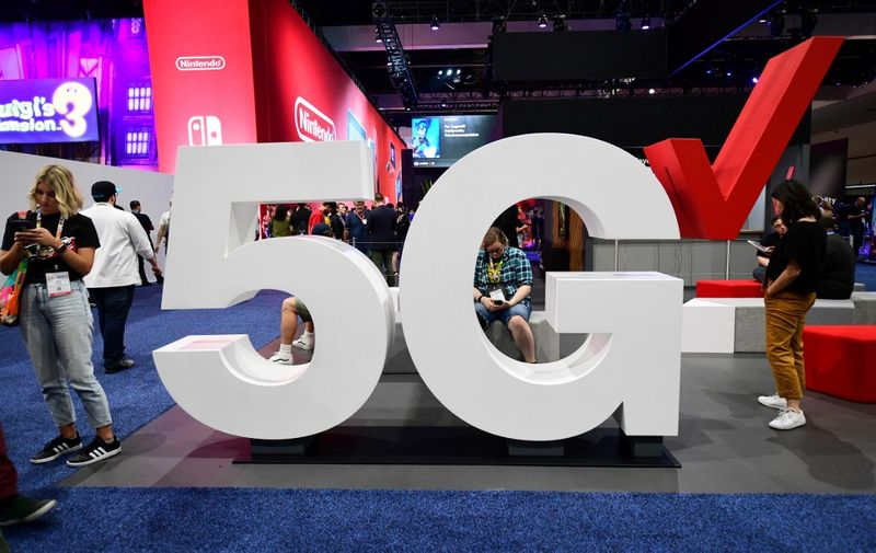 Cellphone users stand beside a Verizon 5G display at the 2019 Electronic Entertainment Expo, also known as E3, on June 12, 2019 in Los Angeles, California. - Gaming fans and developers gather, connecting thousands of the brightest, best and most innovative in the interactive entertainment industry and a chance for many to preview new games. (Photo by Frederic J. BROWN / AFP)