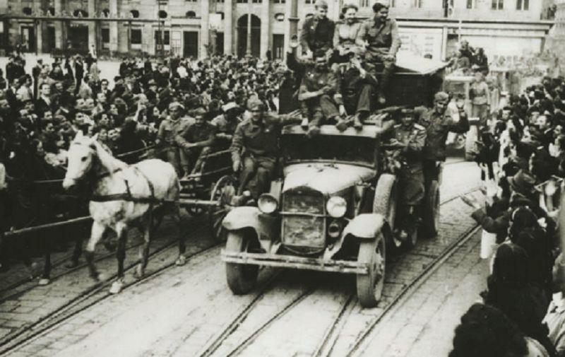 Kroz masu okupljenih građana iz Jurišićeve ulice na Trg pristiže kolona partizanskih kamiona i zaprežnih vozila s partizanima