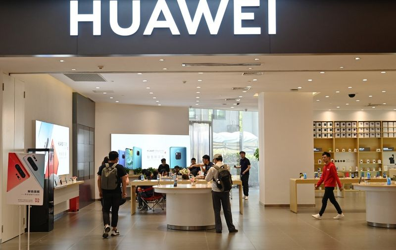 People browse for items in a Huawei store in a shopping mall in Shanghai on May 22, 2019. (Photo by Hector RETAMAL / AFP)
