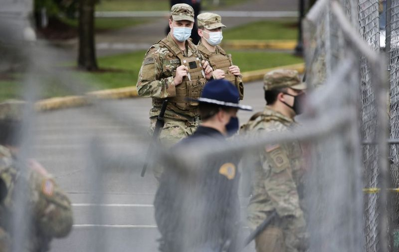 Members of the Washington National Guard stand outside the state Capitol in Olympia, Washington on January 17, 2021 during a nationwide protest called by anti-government and far-right groups supporting US President Donald Trump and his claim of electoral fraud in the November 3 presidential election. - The FBI warned authorities in all 50 states to prepare for armed protests at state capitals in the days leading up to the January 20 presidential inauguration of President-elect Joe Biden. (Photo by Jason Redmond / AFP)