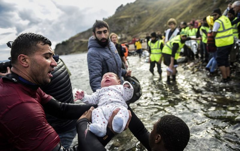 Migrant families - helped by rescuers - disembark on the Greek island of Lesbos after crossing with other migrants and refugees the Aegean Sea from Turkey, on November 25, 2015.  More than 800.000 migrants, mostly fleeing war and persecution in Syria, Iraq and Afghanistan, have crossed the Mediterranean this year to reach Europe. AFP PHOTO / BULENT KILIC / AFP PHOTO / BULENT KILIC