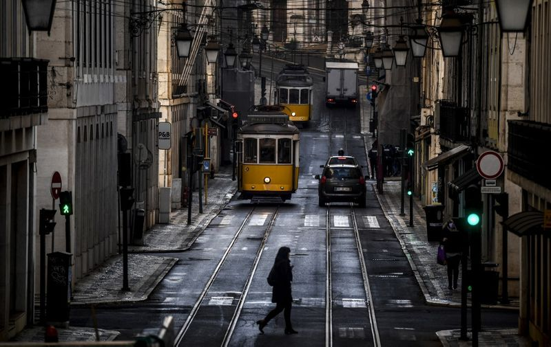 A woman crosses a street past trams in Lisbon on January 15, 2021 as Portugal entered a fresh lockdown over a surge in coronavirus cases. - The novel coronavirus has killed at least 1,994,833 people since the outbreak emerged in China in December 2019, according to a tally from official sources compiled by AFP. (Photo by PATRICIA DE MELO MOREIRA / AFP)