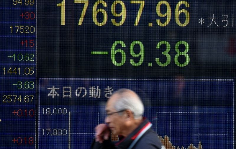 A man walks past an electric quotation board flashing the Nikkei key index of the Tokyo Stock Exchange (TSE) in front of a securities company in Tokyo on January 8, 2016. Tokyo's benchmark stock index started 2016 with a record New Year losing streak, as growing concerns about China's economy and geopolitical tensions battered investor spirits.      AFP PHOTO/Toru YAMANAKA / AFP / TORU YAMANAKA