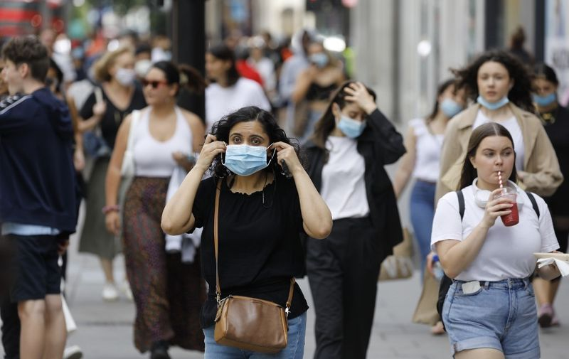 A shopper adjusts her face mask on Oxford Street om London on July 24, 2020, after wearing facemasks in shops and supermarkets became compulsory in England as a measure to combat the spread of the novel coronavirus. (Photo by Tolga AKMEN / AFP)