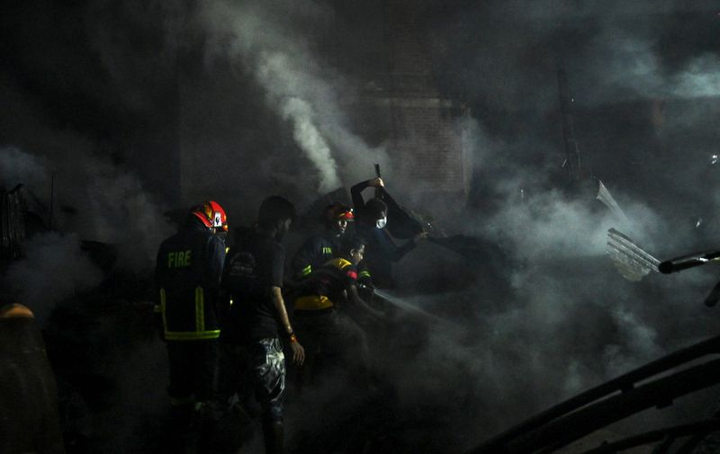 Civilians and firefighters work to extinguish a fire that broke out in a slum in Dhaka on October 30, 2020. (Photo by Munir Uz zaman / AFP)