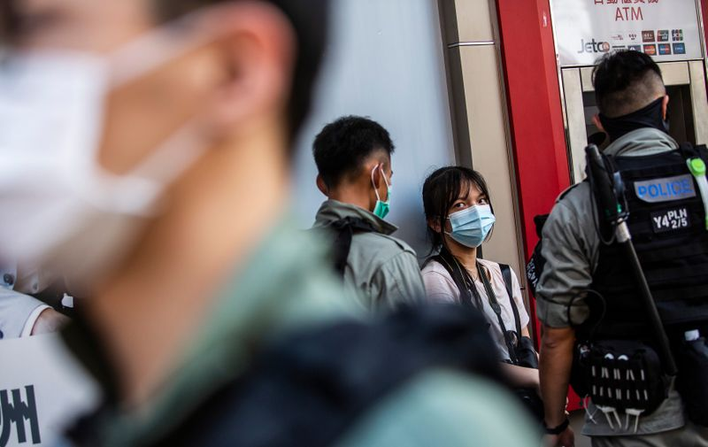 Police stop and search a woman (C) during a protest against China's planned national security law in Hong Kong on June 28, 2020.,Image: 536686150, License: Rights-managed, Restrictions: , Model Release: no