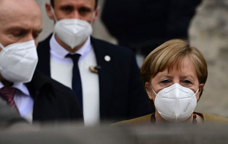 German Chancellor Angela Merkel (R) leaves the Reichstag building, seat of the German lower house of parliament Bundestag, during a session in Berlin on March 4, 2021. (Photo by Tobias Schwarz / AFP)