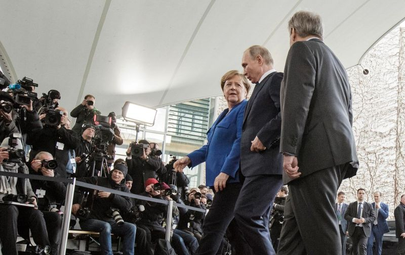 """German Chancellor Angela Merkel (L) welcomes Russian President Vladimir Putin (C) next to Secretary-General of the United Nations (UN) Antonio Guterres (R) before the Peace summit on Libya at the Chancellery in Berlin on January 19, 2020. - World leaders gather in Berlin on January 19, 2020 to make a fresh push for peace in Libya, in a desperate bid to stop the conflict-wracked nation from turning into a """"second Syria"""". Chancellor Angela Merkel will be joined by the presidents of Russia, Turkey and France and other world leaders for talks held under the auspices of the United Nations. (Photo by Carsten Koall / dpa / AFP) / Germany OUT"""