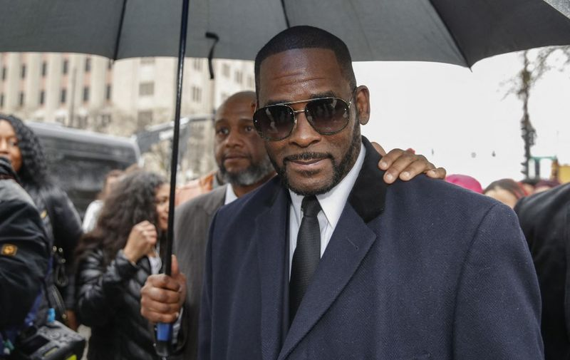 """(FILES) In this file photo taken on May 07, 2019, R. Kelly leaves the Leighton Criminal Court Building after a hearing on sexual abuse charges in Chicago, Illinois. - R. Kelly is a """"predator"""" who used his fame to groom minors for sex, prosecutors told a New York court as the disgraced R&B superstar's much-anticipated trial got underway on August 18, 2021. The Grammy-winning artist -- wearing a gray suit, purple tie, and glasses -- sat silently, his head down at times as the prosecution opened its case by detailing a pattern of violent abuse. (Photo by KAMIL KRZACZYNSKI / AFP)"""