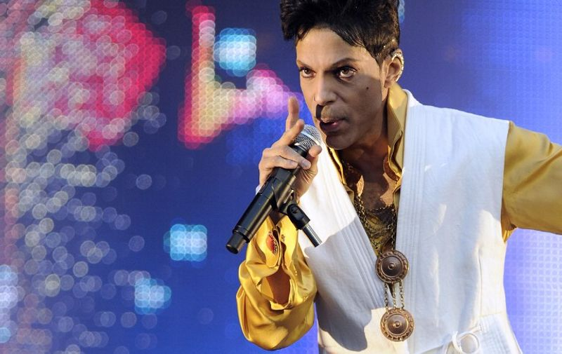 (FILES) This file photo taken on June 30, 2011 shows US singer and musician Prince performing on stage at the Stade de France in Saint-Denis, outside Paris.   Pop icon Prince -- one of the most influential but elusive figures in music -- has died at his compound in Minnesota, entertainment website TMZ reported on April 21, 2016, citing unnamed sources. Local authorities said a death investigation was underway at Prince's Paisley Park complex, but did not give the identity of the fatality.  / AFP PHOTO / BERTRAND GUAY