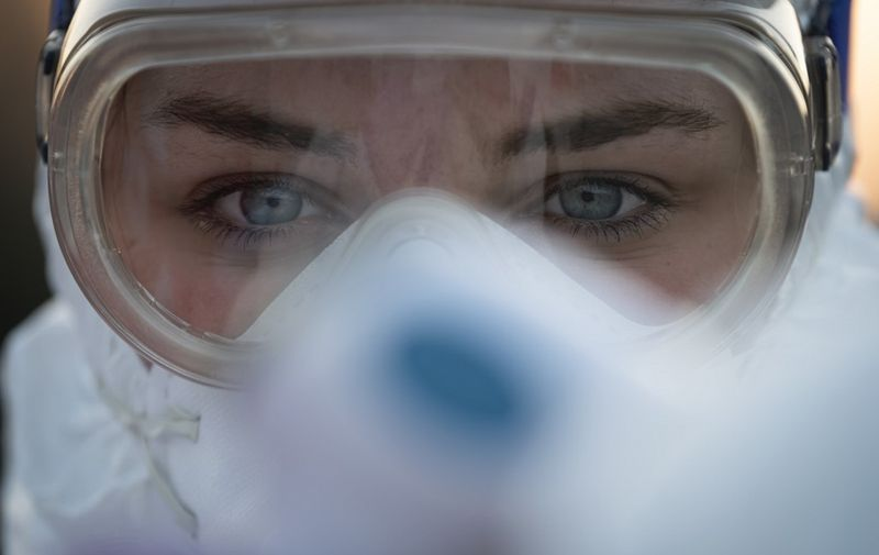 A medical worker wears protective goggles as she prepares to measure motorists' body temperatures  at the Slovenian-Italian border crossing near Nova Gorica, on March 11, 2020, after Slovenia's government announced it would close its border with Italy, hard hit by the outbreak of COVID-19, the new coronavirus. - Italy's neighbours Austria and Slovenia announced on March 10 Tuesday strict travel restrictions and other measures in the wake of similar moves by Rome to limit the spread of the new coronavirus. (Photo by Jure Makovec / AFP)