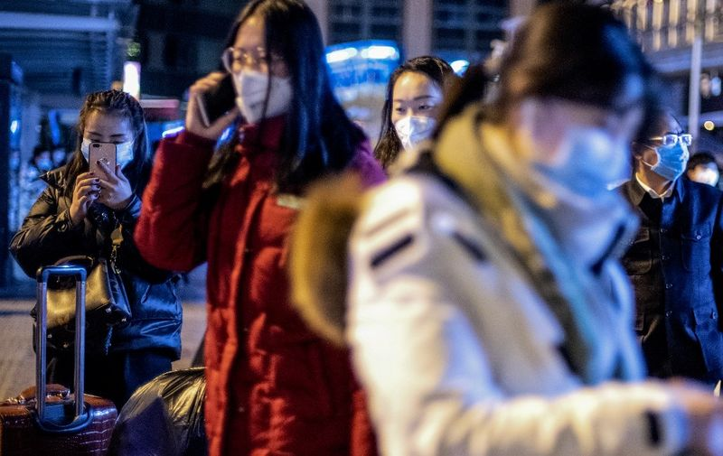 People wearing protective masks arrive at Beijing railway station ahead of the Lunar New Year in Beijing on January 23, 2020. - China is halting public transport and closing highway toll stations in two more cities in Hubei province, the epicentre of a deadly virus outbreak, authorities said on January 23. (Photo by NOEL CELIS / AFP)