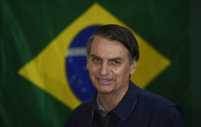 Brazil's right-wing presidential candidate for the Social Liberal Party (PSL) Jair Bolsonaro walks in front of the Brazilian flag as he prepares to cast his vote during the general elections, in Rio de Janeiro, Brazil, on October 7, 2018. Polling stations opened in Brazil on Sunday for the most divisive presidential election in the country in years, with far-right lawmaker Jair Bolsonaro the clear favorite in the first round. About 147 million voters are eligible to cast ballots and choose who will rule the world's eighth biggest economy. New federal and state legislatures will also be elected. / AFP PHOTO / Mauro PIMENTEL