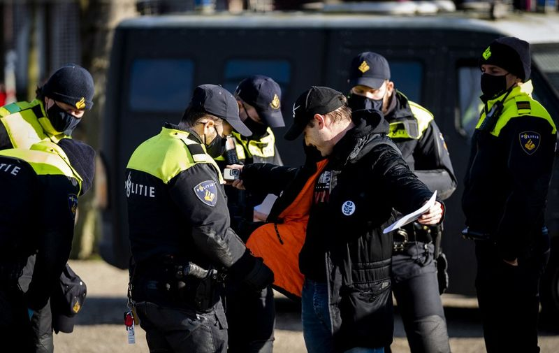A man is being checked by police officers on the Museumplein in Amsterdam on January 31, 2021 as Nederland in Verzet action group called for a protest against the Covid-19 guidelines. (Photo by STRINGER / ANP / AFP) / Netherlands OUT