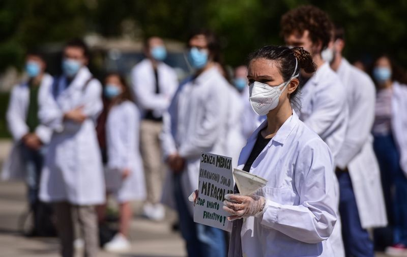 A medical student holds a placard reading 'Without doctors, only miracles remain' during a protest of medical students, newly qualified doctors and doctors in training outside Milan's Central railway station on May 29, 2020, asking for an educational reform of medical training, as the country eases its lockdown measures aimed at curbing the spread of the COVID-19 infection, caused by the novel coronavirus. (Photo by Piero Cruciatti / AFP)