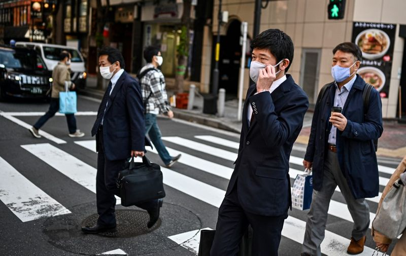 People walk on a pedestrian crossing in Tokyo on November 16, 2020, as government data showed Japan's economy exited recession in the third quarter, growing a better-than-expected 5.0 percent following a record contraction. (Photo by Charly TRIBALLEAU / AFP)