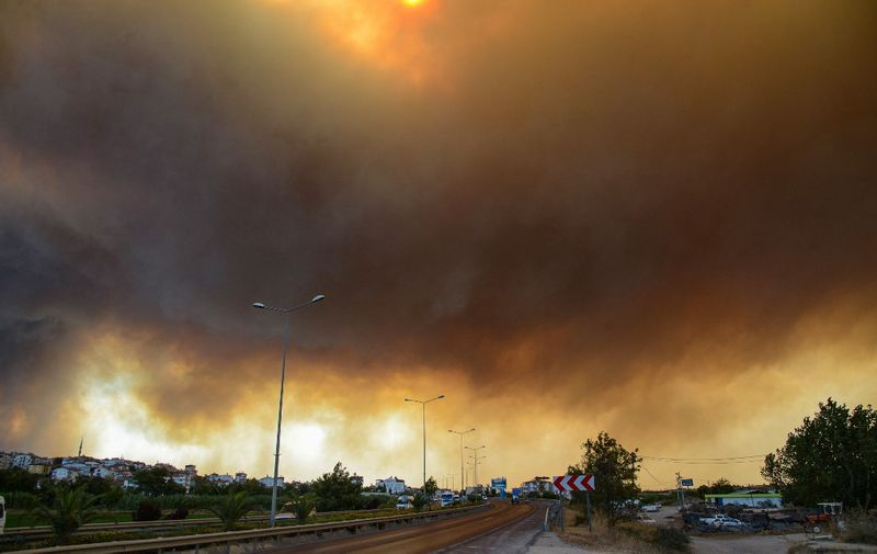 Heavy clouds of smoke rise from a massive forest fire which  engulfed a Mediterranean resort region on Turkey's southern coast near the town of Manavgat, on July 29, 2021. - At least three people were reported dead on July 29, 2021 and more than 100 injured as firefighters battled blazes engulfing a Mediterranean resort region on Turkey's southern coast. Officials also launched an investigation into suspicions that the fires that broke out Wednesday in four locations to the east of the tourist hotspot Antalya were the result of arson. (Photo by Ilyas AKENGIN / AFP)