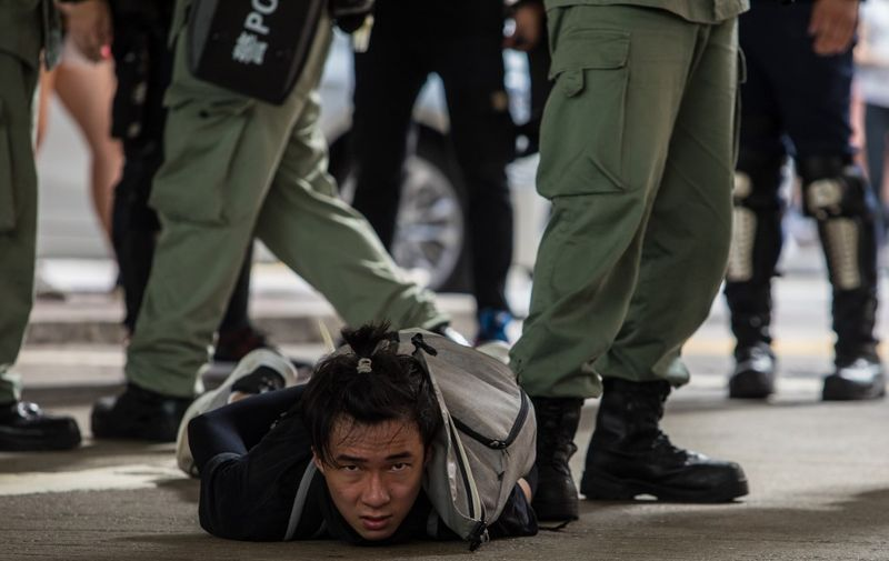 Riot police detain a man as they clear protesters taking part in a rally against a new national security law in Hong Kong on July 1, 2020, on the 23rd anniversary of the city's handover from Britain to China. - Hong Kong police made the first arrests under Beijing's new national security law on July 1 as the city greeted the anniversary of its handover to China with protesters fleeing water cannon. (Photo by DALE DE LA REY / AFP)