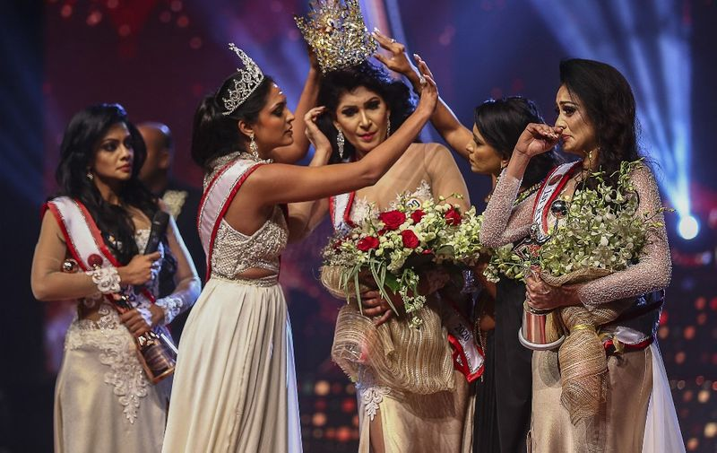 In this photograph taken on April 4, 2021, winner of Mrs. Sri Lanka 2020 Caroline Jurie (2-L) removes the crown of 2021 winner Pushpika de Silva (C) as she is disqualified by the jurie over the accusation of being divorced, at a beauty pageant for married women in Colombo. (Photo by - / AFP)