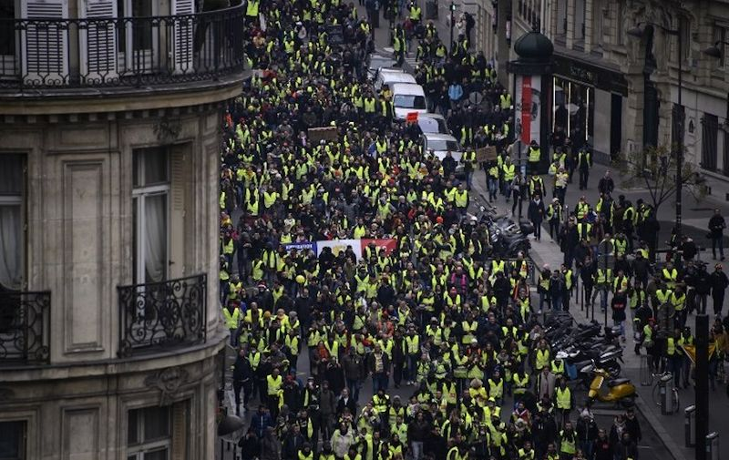 """Yellow vest """"Gilets Jaunes"""" march along Rue Quatre September in Paris on January 5, 2019, during a rally by the anti-government protestors. - France's """"yellow vest"""" protestors were back on the streets as a government spokesman denounced those still protesting as hard-liners who wanted only to bring down the government. Several hundred protestors gathered on the Champs Elysees in central Paris, where around 15 police wagons were also deployed, an AFP journalist said. Marches were underway in several other cities across France. (Photo by Olivier MORIN / AFP)"""