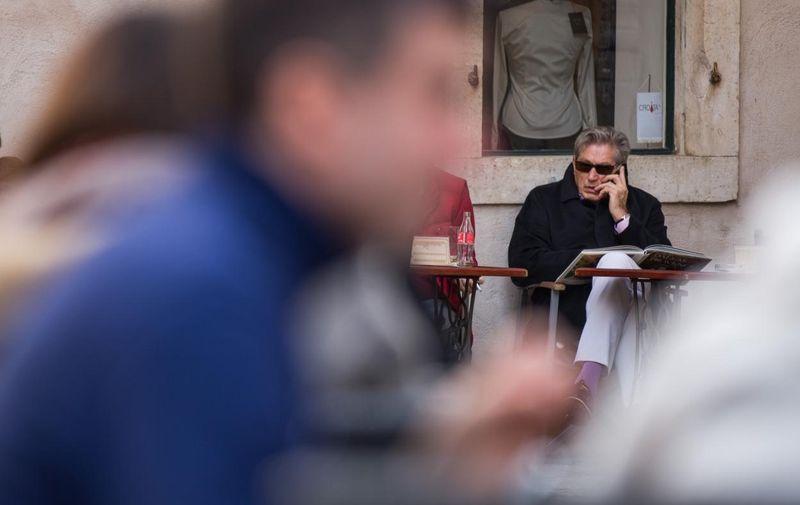 31.01.2012., Stradun, Dubrovnik - Uz kolendu na Silvestrovo, gradonacelnik Dubrovnika Andro Vlahusicć uputio je svima cestitku, a nakon cocktail showa dubrovackih barmena uz nastup klape Ragusa, na rasporedu se nasla i Djecja Nova godina uz Sanju Dolezal i Nove Fosile. Tomislav Horvatincic uz kavu i knjigu u legendarnom Trubaduru. Iako je dosao u pratnji dame kavu je popio sam.  Photo: Grgo Jelavic/PIXSELL