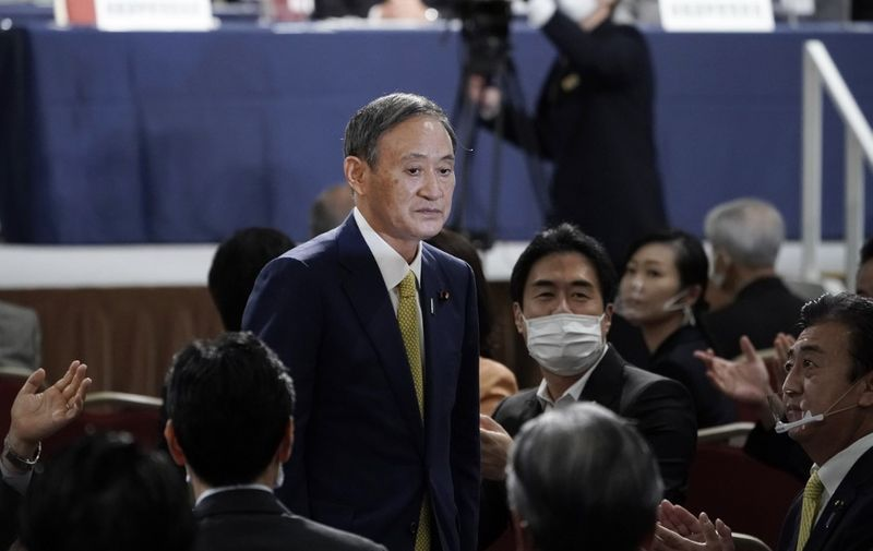 Japan's Chief Cabinet Secretary Yoshihide Suga gestures after being elected as new head of Japan's ruling Liberal Democratic Party at the party's leadership election in Tokyo on September 14, 2020. - Japan's ruling party votes on September 14 for its next leader, with top government adviser Yoshihide Suga all but certain to win and replace Shinzo Abe as the country's new prime minister. (Photo by Eugene Hoshiko / POOL / AFP)