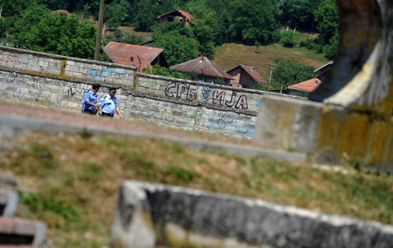 """Bosnian Serb police officers walk past a Cyrillic graffito reading """"Serbia"""" in Bratunac, near Srebrenica, on July 11, 2012. Bosnians on Wednesday buried 520 victims of the 1995 Srebrenica massacre, with the two alleged masterminds of the slaughter finally on trial for genocide. About 30,000 people were gathered at a special memorial centre in Potocari, just outside Srebrenica, for the mass funeral on the 17th anniversary of the worst atrocity on European soil since World War II.  AFP PHOTO / ANDREJ ISAKOVIC"""