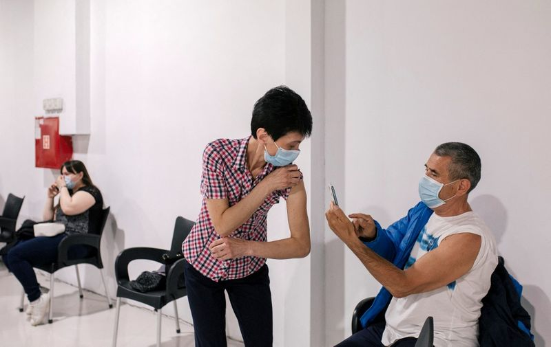 A patient has her arm photographed after receiving a dose of a coronavirus (Covid-19) vaccine at a vaccination centre in a shopping mall of Belgrade on May 6, 2021. - Serbia's president said on May 5, 2021, that his country would pay each citizen who gets a Covid jab before the end of May, in what could be the world's first cash-for-jabs scheme. The Balkans country bought millions of doses -- from Western firms as well as China and Russia -- and briefly became a regional vaccine hub when it offered foreigners the chance to be inoculated. (Photo by Vladimir Zivojinovic / STR / AFP)