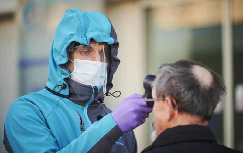 A medical worker measures body temperature at one of the entrances of the Community Health Centre in Kranj, Slovenia on March 23, 2020 amid concerns over the spread of the COVID-19 coronavirus. (Photo by Jure Makovec / AFP)
