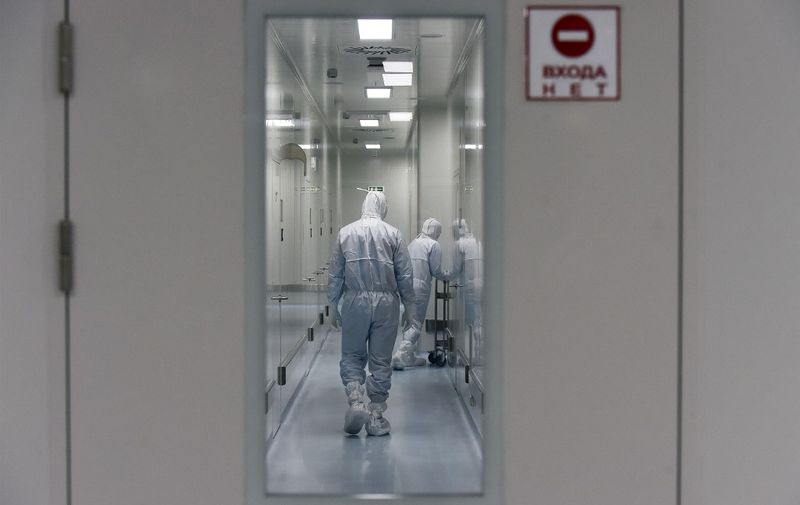 Employees wearing protective equipment walk in a passage at the headquarters of Russia's biotech company BIOCAD, which is developing its own vaccine against the new coronavirus and working on another one in cooperation with the country's virus research centre in Siberia, Vektor, in Strelna on May 20, 2020. (Photo by OLGA MALTSEVA / AFP)