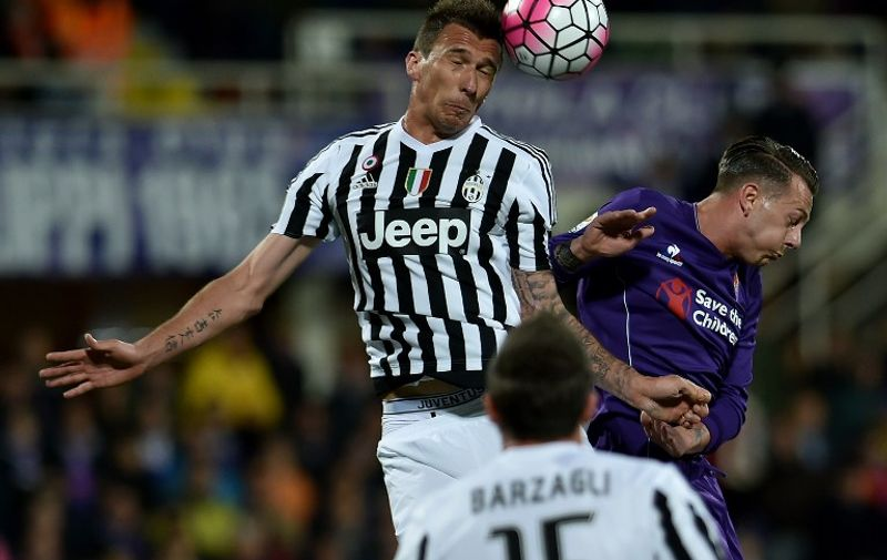 Juventus' forward from Croatia Mario Mandzukic (L) vies with Fiorentina's forward from Italy Federico Bernardeschi during the Italian Serie A football match Fiorentina vs Juventus on April 24, 2016, at Artemio Franchi stadium in Florence.   / AFP PHOTO / ALBERTO PIZZOLI
