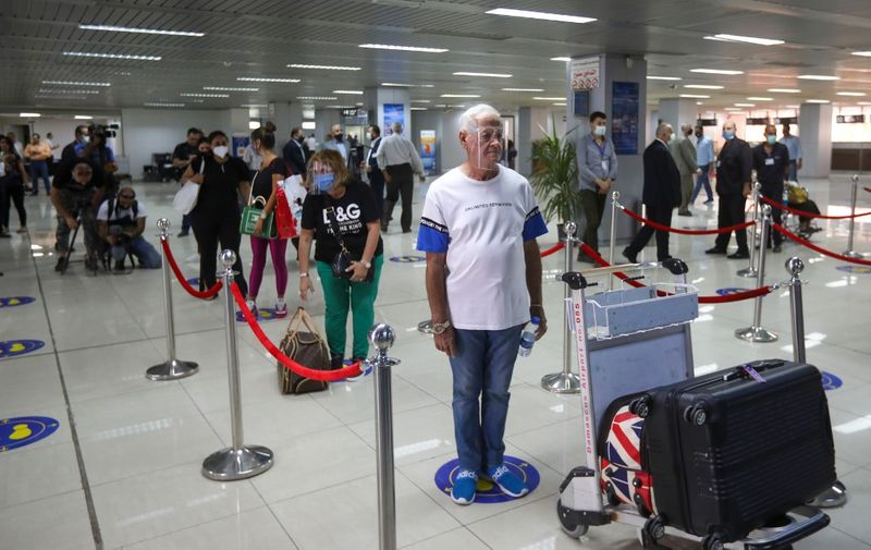 Passengers, wearing protective face masks, queue at the Damascus International airport in the Syrian capital on October 1, 2020. (Photo by LOUAI BESHARA / AFP)