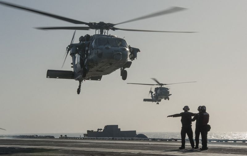 This US Navy photo released January 15, 2015 shows an MH-60S Sea Hawk helicopter from the Red Lions of Helicopter Sea Combat Squadron (HSC) 15 as it prepares to land on the flight deck of the Nimitz-class aircraft carrier USS Carl Vinson (CVN 70) on January 13, 2015 in the Gulf. Carl Vinson is deployed in the US 5th Fleet area of responsibility supporting Operation Inherent Resolve, maritime security operations, strike operations in Iraq and Syria as directed, and theater security cooperation efforts in the region. AFP PHOTO/US NAVY/JOHN PHILIP WAGNER, JR./HANDOUT (Photo by John Philip Wagner, Jr. / Navy Media Content Services / AFP)