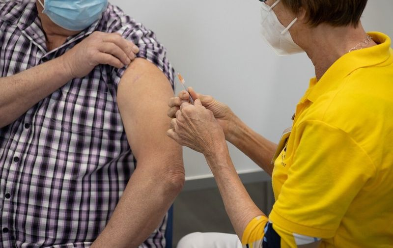 A man is vaccinated by a medical healthcare worker, holding and pressing the syringe jab to the arm. New XL Vaccination center against Covd coronavirus in Helmond from the Municipal Health Service GGD, Dutch Gemeentelijke Gezondheidsdienst, a decentralised public health care organisation. The new vaccination center, a converted factory - warehouse is part of the Dutch vaccination program against COVID-19, the system invites people to get the jab with a target for everyone over 18 to be invited in 2021. The new facility in Helmond opened on Saturday 24 April 2021, offering the BioNTech Pfizer vaccine with the capability to vaccinate over 5000 people per day in the 13+ lines. The Netherlands is opening more mega centers trying to ramp up the immunization process of the population to provide safety against the spread of the pandemic. Helmond, The Netherlands on April 24, 2021 COVID Vaccination In The Netherlands, Helmond - 24 Apr 2021,Image: 607902754, License: Rights-managed, Restrictions: , Model Release: no, Credit line: Profimedia