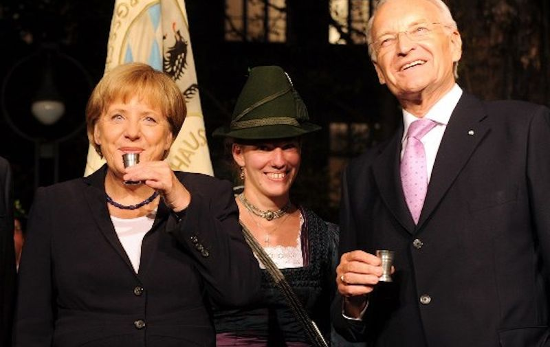 German Chancellor Angela Merkel (C) drinks a schnapps beside President of the European Commission Emanuel Barroso (L) and former Bavarian State Governor Edmund Stoiber (R) ahead OF a ceremony for Edmund Stoiber on the occasion of his 70th birthday in Munich, southern Germany, on September 28, 2011.  AFP PHOTO/CHRISTOF STACHE (Photo by CHRISTOF STACHE / AFP)