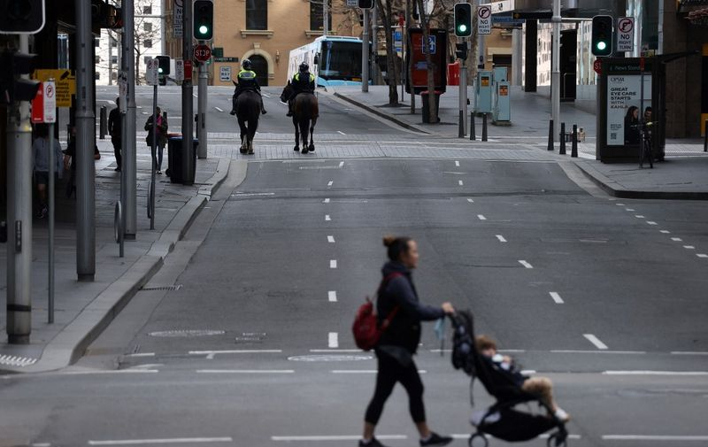 A woman makes her way through a quiet street in the central business district of Sydney on July 31, 2021, as authorities race to contain an emerging outbreak of the Delta strain. (Photo by DAVID GRAY / AFP)