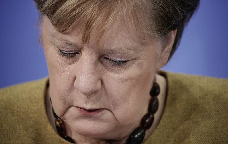German Chancellor Angela Merkel looks down during a press conference following talks via video conference with Germany's state premiers on the extension of the current partial lockdown, at the Chancellery in Berlin on January 5, 2021. - Germany on January 5 prolonged and toughened up its partial lockdown with tighter limits on social contacts, as Europe's top economy struggles to battle stubbornly high coronavirus infections. Schools, leisure and sporting facilities and most shops will remain shut through to January 31, the German Chancellor said after talks with leaders of Germany's 16 states. (Photo by Michael Kappeler / POOL / AFP)