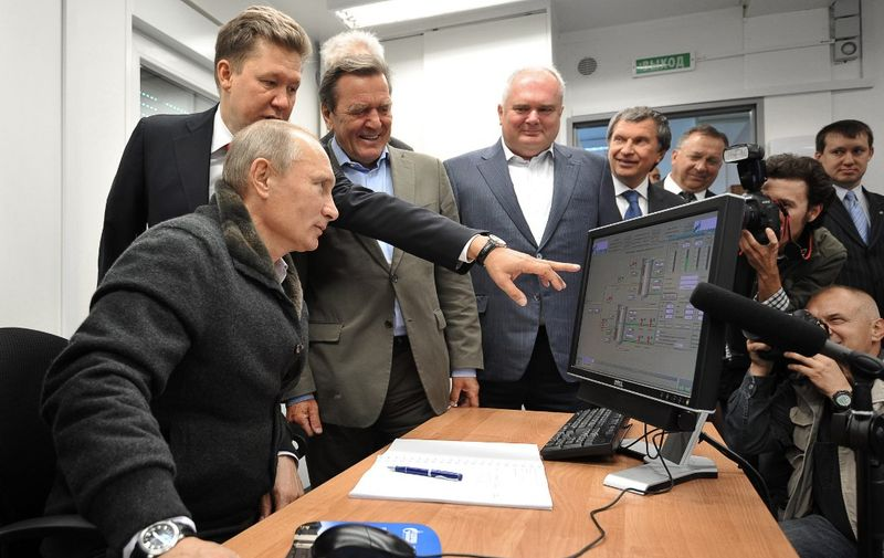 """Russian Prime Minister Vladimir Putin (L),Gazprom Chief Executive Officer Alexei Miller (2nd L) and former German chancellor Gerhard Schroeder (3rd L) look at a screen as they attend the inauguration of the Nord Stream Project information mount at the gas compressor station """"Portovaya"""" outside Vyborg, September 6, 2011. Vladimir Putin launched the Nord Stream pipeline, designed to bring Russian natural gas to Germany via the bed of the Baltic Sea and to avoid shipments through central Europe. After gas fills the pipeline, Russia will start gas shipments in Europe. AFP PHOTO / RIA NOVOSTI / POOL / ALEXEY NIKOLSKY (Photo by ALEXEY NIKOLSKY / RIA NOVOSTI / AFP)"""