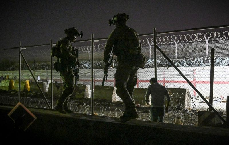 In this picture taken in the late hours on August 22, 2021 British and Canadian soldiers stand guard near a canal as Afghans wait outside the foreign military-controlled part of the airport in Kabul on August 23, 2021, hoping to flee the country following the Taliban's military takeover of Afghanistan. (Photo by WAKIL KOHSAR / AFP)