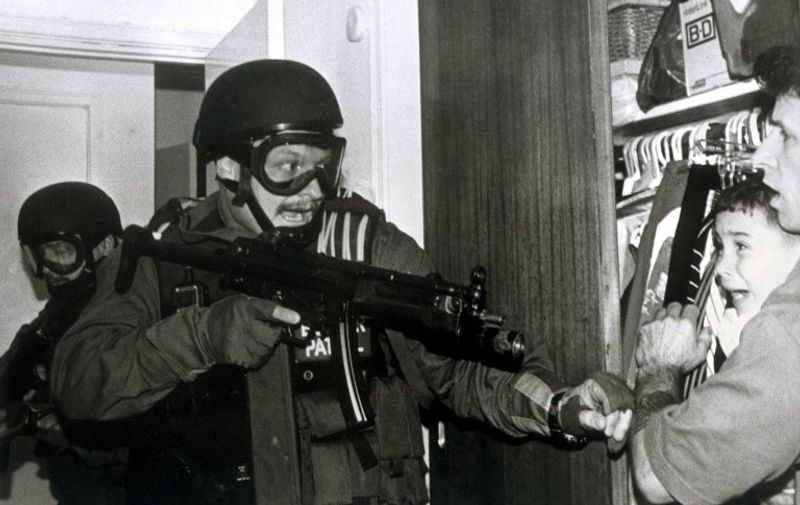 This photograph released 16 April 2001 by Columbia University in New York and taken by Alan Diaz of the Associated Press, which won the Pulitzer Prize for Breaking News Photography. The photo shows Cuban refugee Elian Gonzalez and Donato Dalrymple (R) in a bedroom closet as federal agents enter the Miami home of Elian's relatives and was taken 22 April 2000.  AFP PHOTO/Alan Diaz/Associated Press