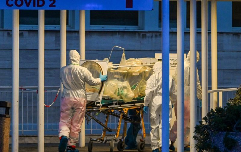 Medical workers in overalls stretch a patient under intensive care into the newly built Columbus Covid 2 temporary hospital to fight the new coronavirus infection, on March 16, 2020 at the Gemelli hospital in Rome. (Photo by ANDREAS SOLARO / AFP)