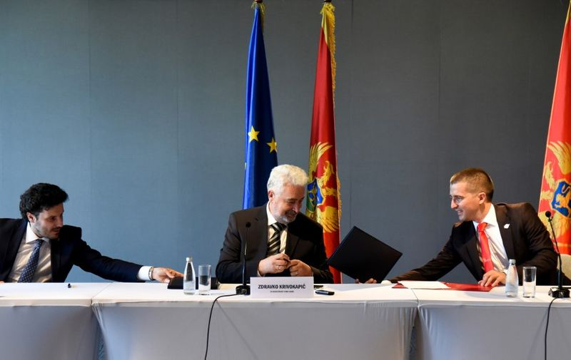 (L-R) Montenegro's opposition leaders, Dritan Abazovic of the liberal Black on White party, Zdravko Krivokapic of the main pro-Serb For the Future of Montenegro and Aleksa Becic of the centrist Democratic Montenegro sign an agreement in Podgorica on September 9, 2020, to form a coalition. - Montenegro's three opposition coalitions formally united on September 9 in hopes of ending the 30-year-run of a ruling party, with pledges to keep the EU candidate country on its pro-West path. The opposition camps span a broad idealogical spectrum but together hold a wafer-thin majority after last month's parliamentary elections. The largest of the coalitions is led by a pro-Russian and anti-NATO party, followed by a more centrist group and a smaller liberal civic bloc. In a written statement on September 9 they sought to assuage fears of breaking Montenegro's ties with the West, including its 2017 NATO membership. (Photo by Savo PRELEVIC / AFP)