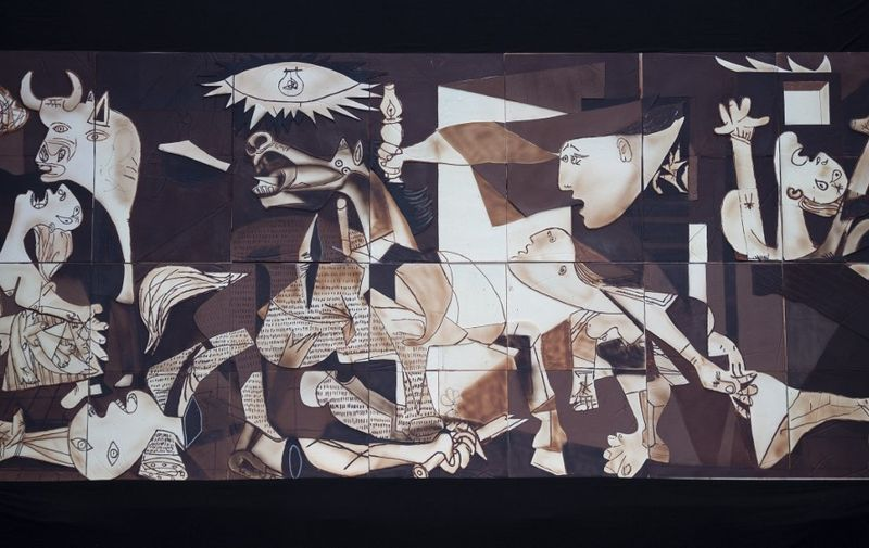 """A life-size chocolate version of Picasso's painting """"Guernica"""" made by members of Euskal Gozogileak (Basque Confectioners) association is pictured during its public presentation in the Spanish Basque town of Gernika on April 25, 2021. - The 7.70 x 3.50 meter chocolate replica of """"Guernica"""" made by around 40 confectioners is exhibited in the town of Gernika to commemorate the 85th anniversary of the bombing raid of the small Basque town by Nazi aircraft, at the behest of General Francisco Franco in 1937. (Photo by ANDER GILLENEA / AFP)"""
