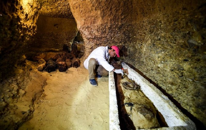 An archaeologist brushes a newly-discovered mummy laid inside a sarcophagus, part of a collection found in burial chambers dating to the Ptolemaic era (323-30 BC) at the necropolis of Tuna el-Gebel in Egypt's southern Minya province, about 340 kilometres south of the capital Cairo, on February 2, 2019. - Egypt's Antiquities Minister said on February 2 that a joint mission from the ministry and Minya University's Archaeological Studies Research Centre found upon a collection of Ptolemaic burial chambers engraved in rock and filled with a large number of mummies of different sizes and genders. The minister added that the newly discovered tombs may be a familial grave for a family from the elite middle class. (Photo by MOHAMED EL-SHAHED / AFP)